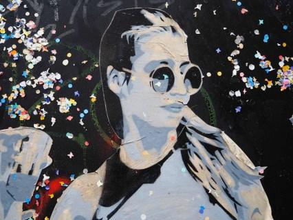 eine Frau mit Sonnebrille und viel Konfetti um sich herum klebt an einer schwarzen Wand
