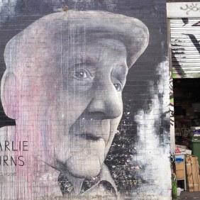 Mural neben einer Garageneinfahr von Ben Slow dass einen alten Mann zeigt