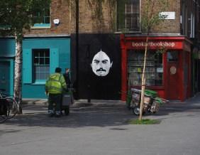 unbekannter weißer Männerkopf auf schwarzem Hintergrund und davor ein Mitarbeiter der Stadtreinigung