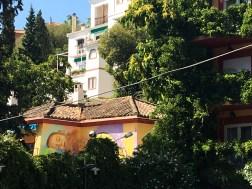 Die Wand eines Kindergartens an der sich hinter viel Grün ein Mural von El Niño de las Pinturas versteckt