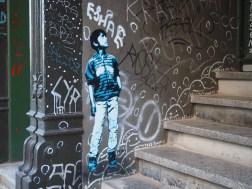 ein Treppenaufgang der mit einem Stencil von Tona versehen ist dass einen Jungen der nach oben sieht zeigt