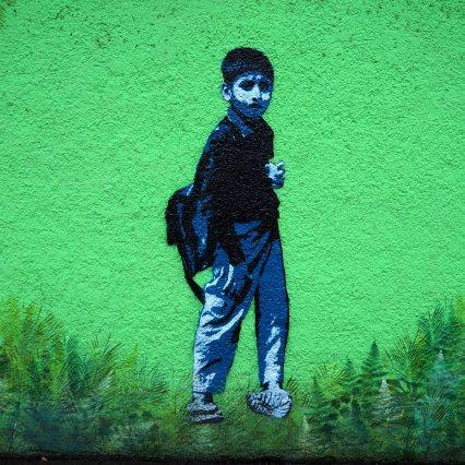 Stencil auf grüner Wand von Tona das einen Schuljungen darstellt