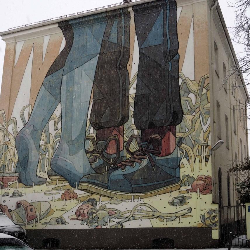 das Mural von Aryz zeigt die Beine eines Paares dass sich vermutlich umarmt