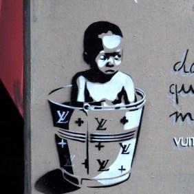 """""""In welcher Welt"""" Stencil von EZK, zeigt einen Jungen in einem Louis Vuitton Eimer"""