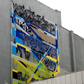 Sowat und Lek haben gelb/blau/schwarze geometrische Muster an die Wand gemalt.