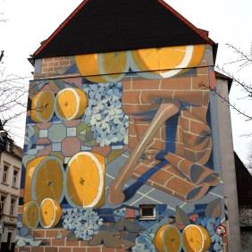 Mural von Aryz dass Orangen und Wände zeigt.