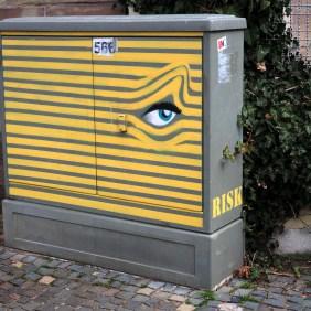 Stromkasten aus dem ein Auge durch gelbe Linien sieht