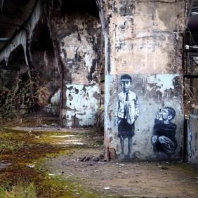 Zwei Jungen hocken auf der Arbeit von Jef Aérosol auf dem Pfeiler einer Brücke.