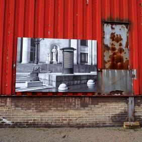 Auf rotem Hintergrund hängt ein Foto von Jordan Seiler.