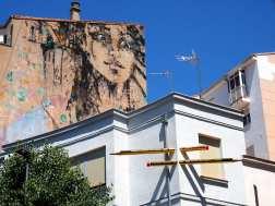 Zweimal Streetart auf einen Foto. Ein Frauenportrait und Bleistift die durch eine Hausecke gehen