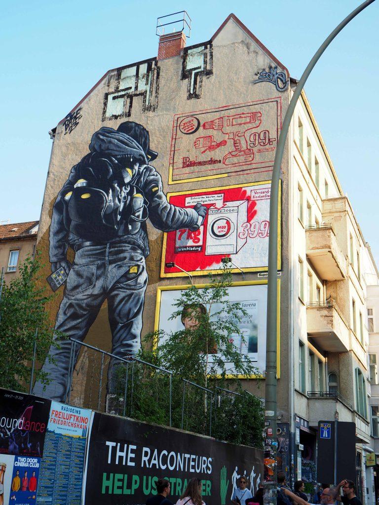 Graffitisprayer übermalt Werbung