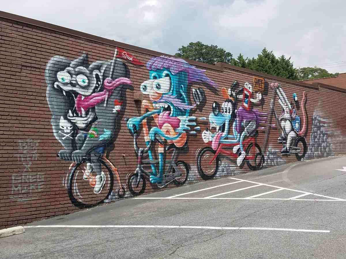 Street art by artists Greg Mike and Big Teeff of characters on bicycles in Midtown Atlanta