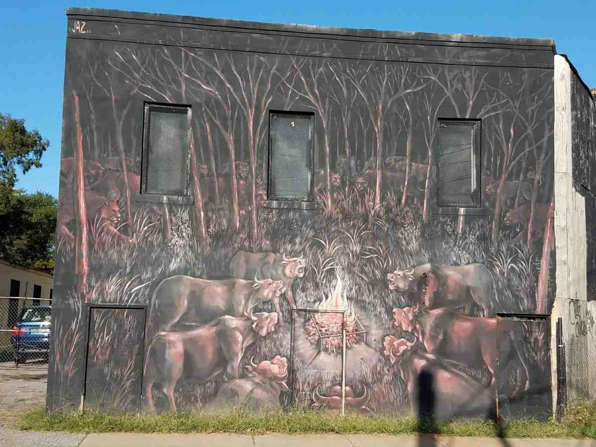 street art featuring Cows gathered around a fire by the artist Jaz
