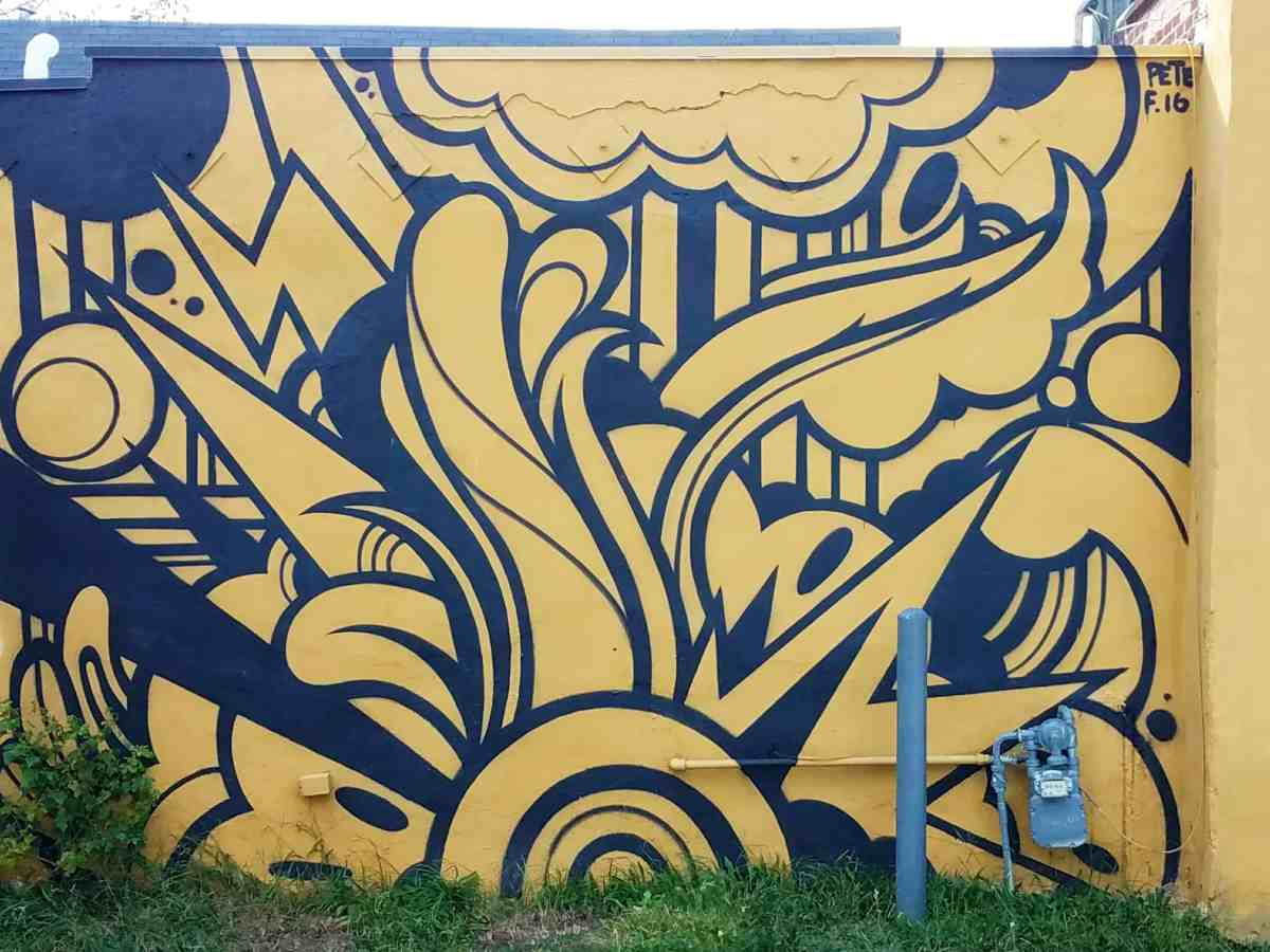 Street art featuring a black and yellow abstract pattern by Peter Ferrari