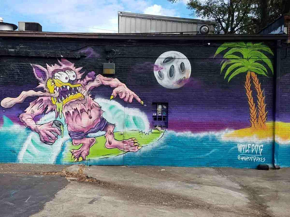Street art by artist Wolfdog featurig a surfer in the moonlight