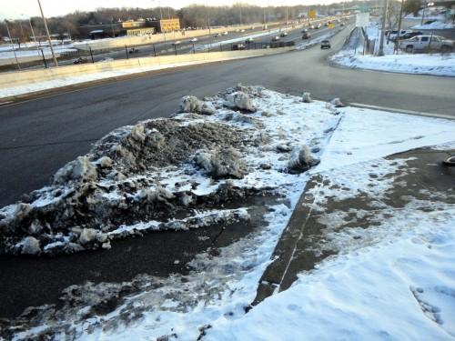 Snow next to Pork Chop island on a freeway on-ramp.