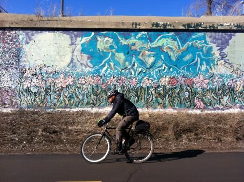 Man rides bicycle on Midtown Greenway.