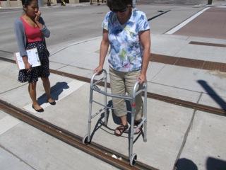 Woman with walker crossing tracks