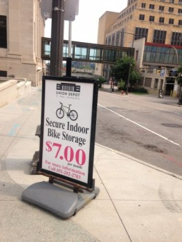 """A sign advertises """"Secure Indoor Bike Storage, seven dollars per month"""" outside of the Union Depot in downtown Saint Paul. The sign is placed on a street corner, and the photo is directed out into the street, which is crossed by a skyway about a block down."""