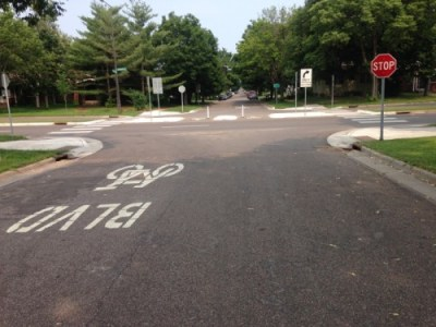 A bicycle symbol is on the pavement in front of the camera, facing towards the camera, a stop sign and a forced right turn for vehicles sign are visible. A busy road has a median which is impregnable to vehicles, but which has two small areas cut out to allow bicycles safe passage.
