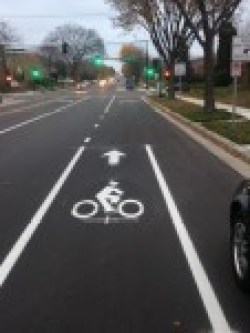 A bike lane is shown, halfway up the photo, the bike lane's solid markings change. The marking on the left side of the bike lane becomes skip striped, and the line closer to the curb disappears altogether. A sign asks drivers to yield to bikes in the right turn lane.