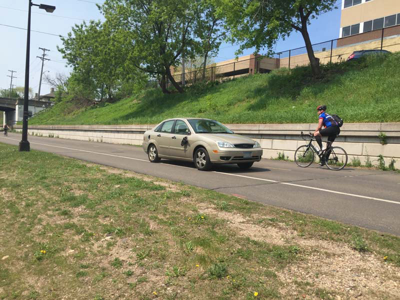 A person driving a car on the Midtown Greenway