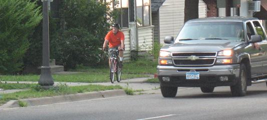 Southbound cyclist riding on the sidewalk towards George Street.