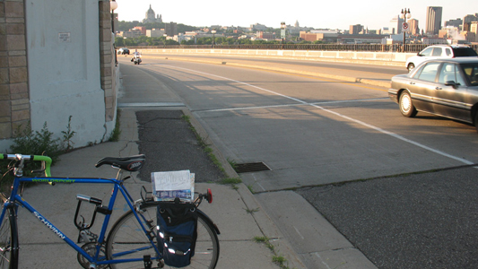 Blind turn at the south end of the bridge, looking northeast. MnDOT plans to widen the sidewalk, add a low barrier between the sidewalk and bike lane, and narrow the bike lane.