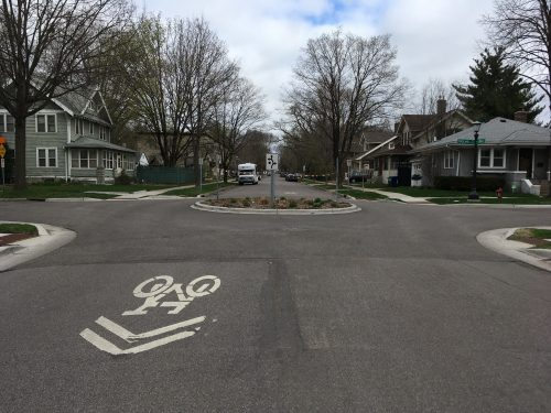 Neighborhood street with arrows and bike symbol on the street and a traffic circle to slow car drivers.