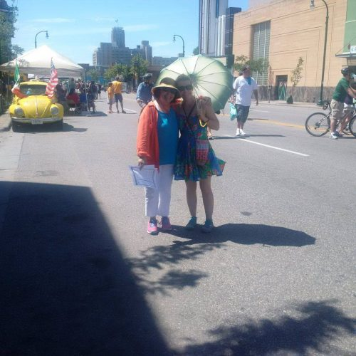 The author stands with her mother in the middle of the street in bright midday sunlight with Midtown Global Market in the background and people milling about on foot and bike. They are facing the camera and Julia holds a parasol.