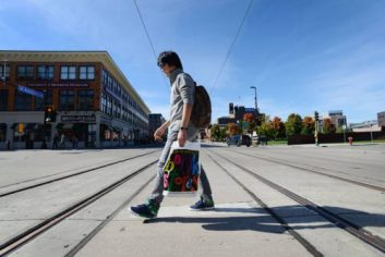 A pedestrian crosses the light rail tracks on the intersection of Oak Street and Washington Avenue on Monday, Oct. 7, 2013. The line is slated for completion in 2014.