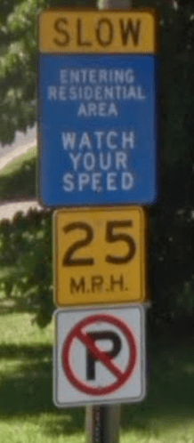 "four signs: ""slow"" ""entering residential area / watch your speed"" ""25 m.p.h"" ""no parking"""
