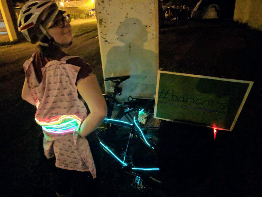 "Me with rainbow light up cape, lit up bike, and custom lawn sign with ""#bancars"" on it"