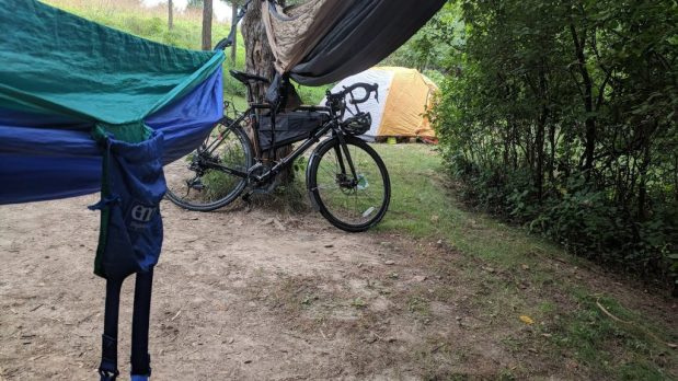 two hammocks, a tent, and a bike leaning against a tree.