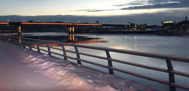 Snow covered bike path with bike basket and bar mitts in foreground. River with railing and bridge, plus dawning sun and grey clouds.