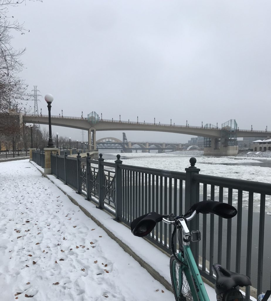 Teal bicycle with snowy bike path, ice-covered Mississippi river, and bridges in the distance