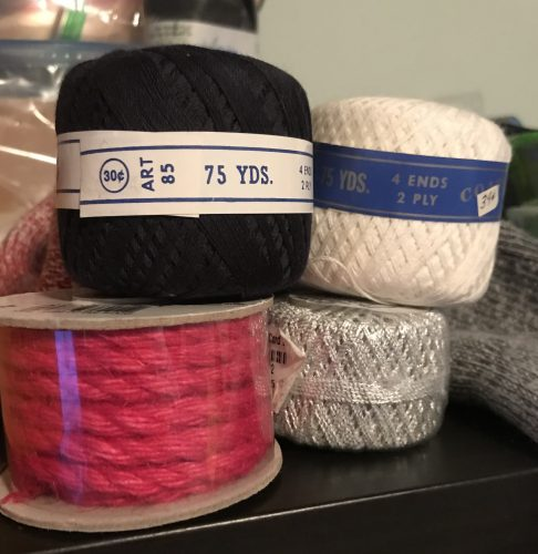 Four spools of thread, including one bright pink rope, one silvery thread, and two cotton threads in white and dark blue