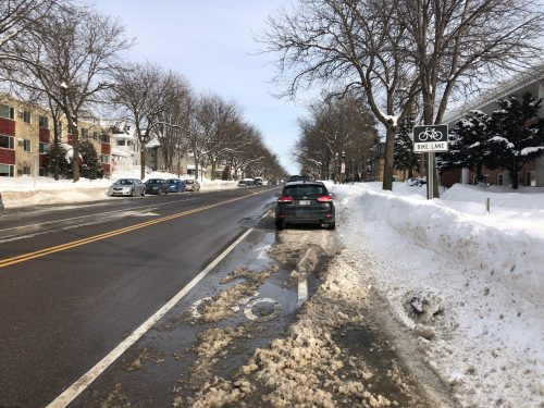 Photo of a car parked in the bike lane while the parking lane is filled with snow