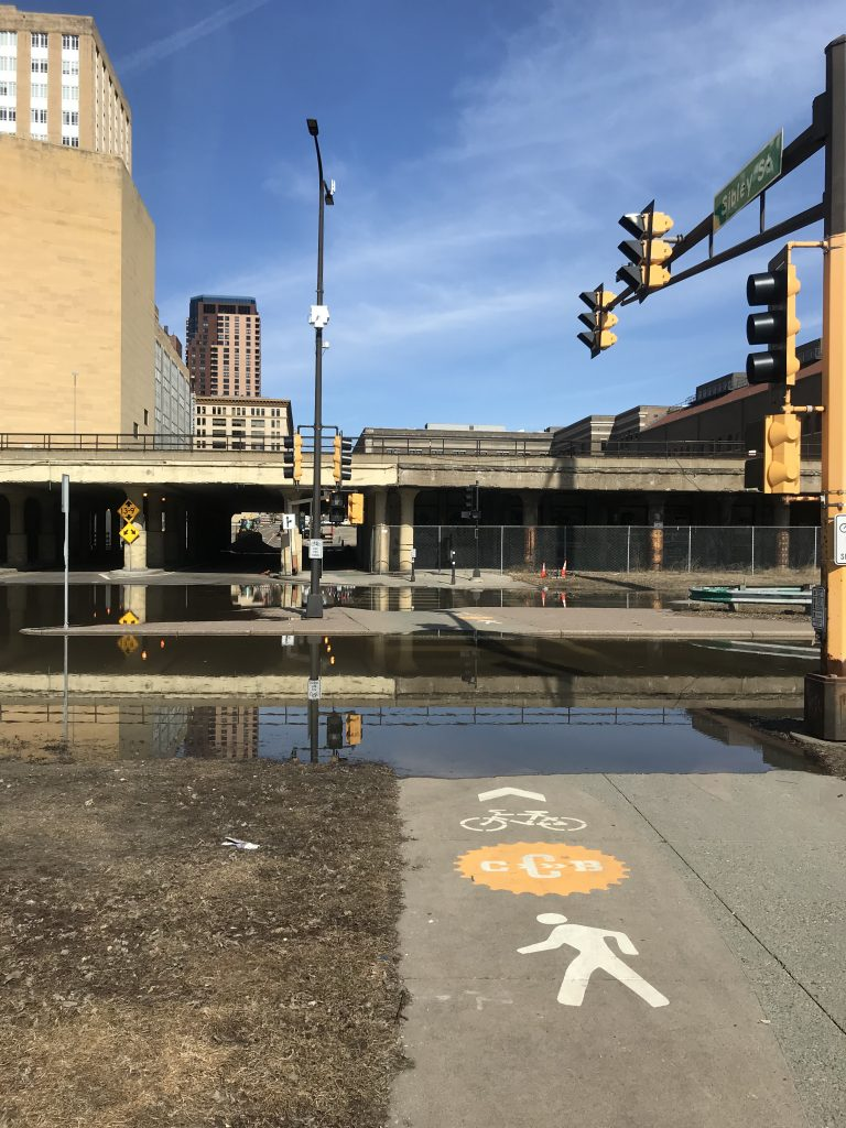 """flooded road with an arrow """"bike/ped"""" pointing toward it"""