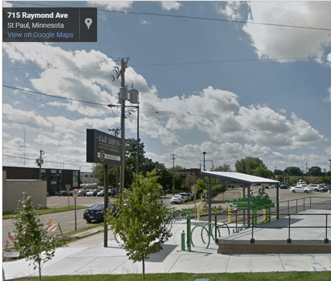Screenshot of google streetview, showing green bicycle racks, a fix-it station, and a covered two-level bicycle rack