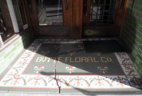 Butte Floral Co, gold tile letters on green background, floral patterned border in red, green, white and gold
