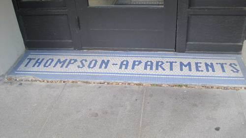 Thompson Apartments in blue letters, white background, blue border