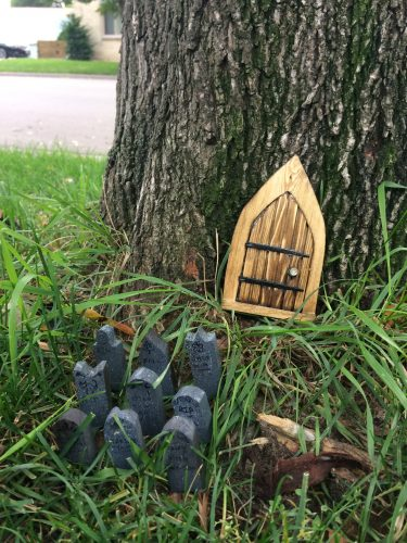 Tiny church door by tree trunk, and nine tiny gravestones with fairy writing