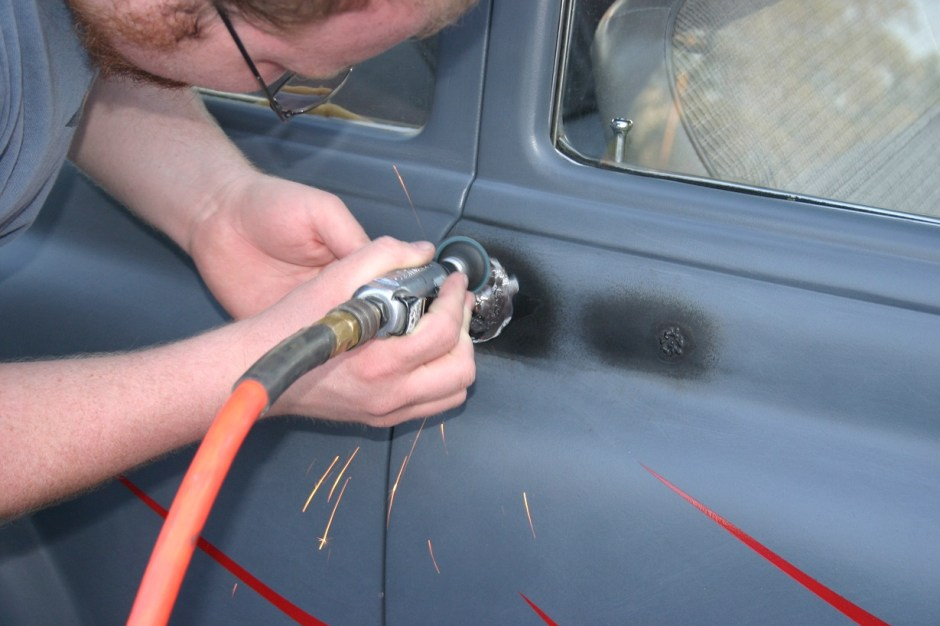 13. Once all the welding is done, a grinder with a 36-grit roloc pad takes the welds down so the door can be smoothed. Again, be careful not to heat it up too much or the metal will warp.