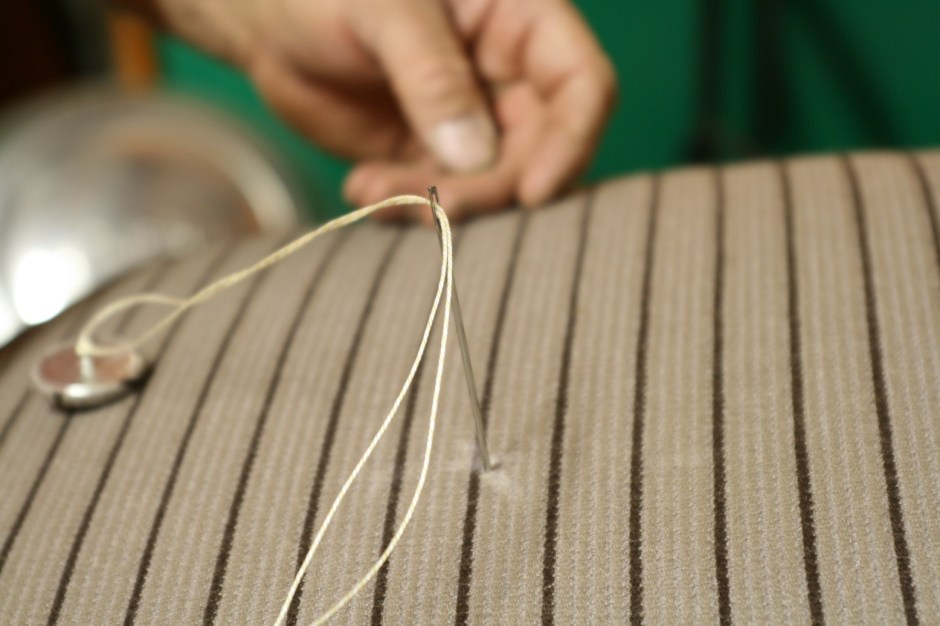 17. The kit comes with a foot-long needle to thread the button through the seat. The string was tied to the button before threading it through the needle.