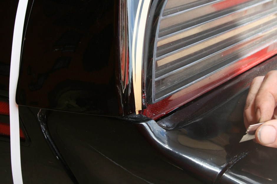 5. Ending the stripes that wrap around the taillights is done by overlapping the narrow stripe on the wide stripe. The excess was then trimmed off.