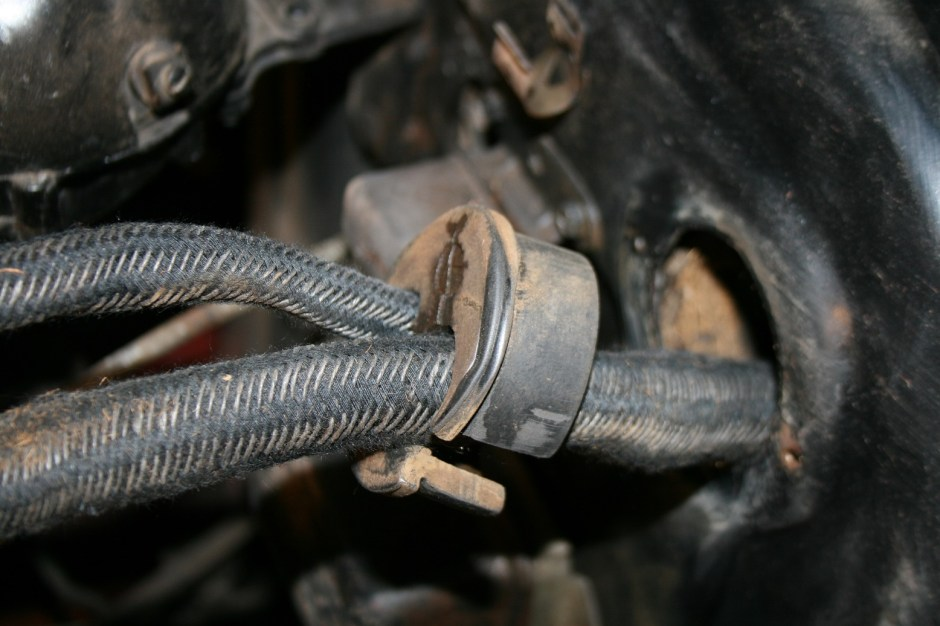13. The engine harness is run through the body plug and the original rubber bushing was re-used.