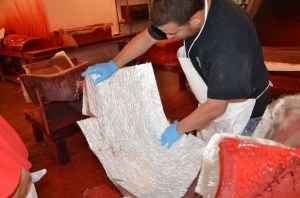 The fiberglass patterns are laid into the molds by hand with a light coat of resin. Some patterns feature cuts for folding so that the finished panel is of a uniform thickness and shape.