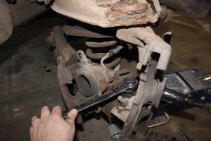 06.Next, the ball joint nuts were removed. Before doing anything, you need to support the lower A-arm with a floor jack, compressing the spring.