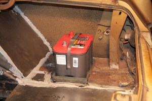 3. This trunk-mounted Optima red top is an AGM (Absorbed Glass Mat) battery, it can be mounted upside down. When mounting a battery, you must always ensure the battery is secure, in this case, a metal bar will go across the top and bolt to the floor of the trunk.